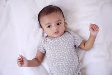 Playful newborn baby lying down in bed