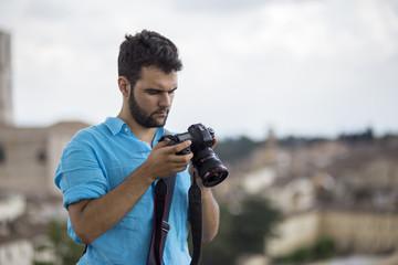 Giovane fotografo con la camicia blu e la barba che guarda le fotografie su una macchina fotografica