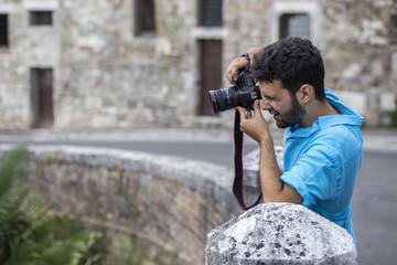 Un ragazzo giovane con la camicia blu e la barba impegnato che realizza una fotografia con una reflex in una strada di Perugia