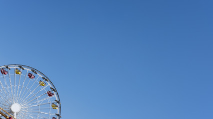Cropped shot of a Ferris wheel against blue clear sky with copy space, concept for freedom, enjoyment, amusement park and nostalgia for childhood fun memories