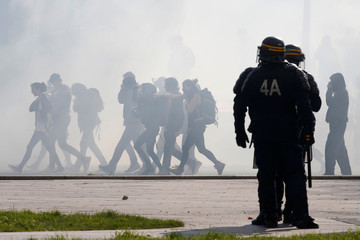Tear gas floats in the air as French CRS riot police face off with protesters during a demonstration in Nantes