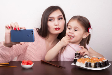 Mom and daughter are eating sushi and taking a selfie with her smart phone