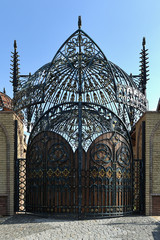 Beautiful oval wrought-iron gates with a dome and wooden inserts, in a fabulous, fantasy style. Forged gates