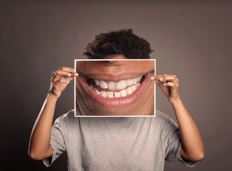 black woman holding a picture of a mouth smiling on a grey background