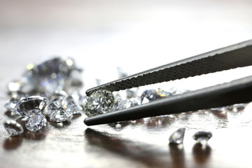 brilliant cut diamond held by tweezers