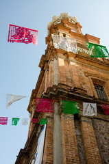 Looking up at the side of the clock tower of Our Lady of Guadalupe with colored flags in foreground in Puerto Vallarta, Mexico