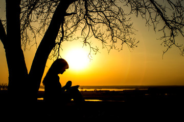 silhouette of woman praying to God in the nature witth the Bible at sunset, the concept of religion and spirituality