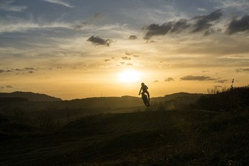 Motorcyclist riding off road during sunset. Slovakia