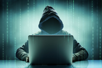 Faceless Anonymous Computer Hacker With Laptop