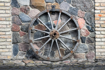 Large ancient wooden cart wheel attached to the wall made of stones.