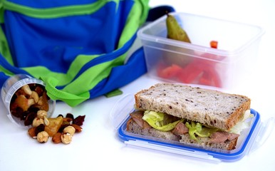 The concept of school food. Lunch box for the student. Sandwich of corn bread with baked turkey and crispy lettuce leaves, pear, nut mix, sweet pepper