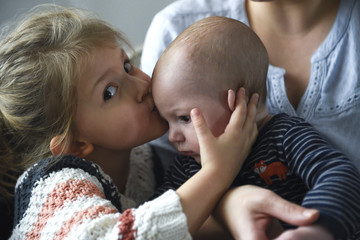 Little girl kissing her baby brother