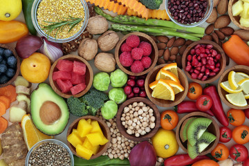 Health food selection with fresh vegetables, fruit, herbs, pulses, seeds and nuts. Super foods concept very high in antioxidants, fibre, smart carbohydrates, anthocyanins and vitamins.