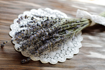 dry lavender bouquet on knitted napkin, wooden table, vintage decoration