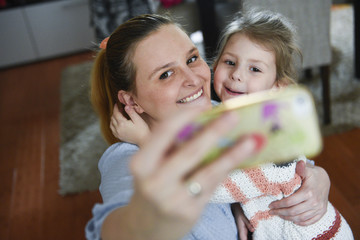 Young mother makes selfie photo with daugther