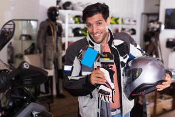 Joyful man in moto jacket is choosing new gloves