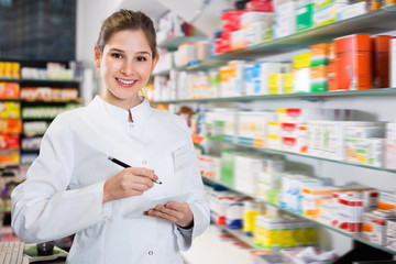 Female specialist is attentively stocktaking medicines with notebook near shelves in pharmacy.