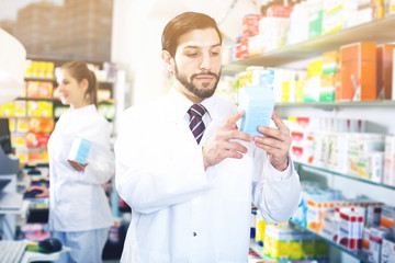 pharmacist standing with medicine on his work place