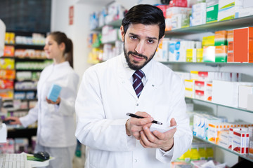 Man apothecary is inventorying medicines