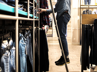 Keuken foto achterwand Fitness man on the ladder picking up jeans from the shelf in the clothes shop
