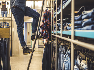 man on the ladder picking up jeans from the shelf in the clothes shop