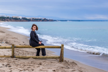 Woman at seaside at cold windy day, Spain