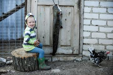 Happy village children play with big catfish