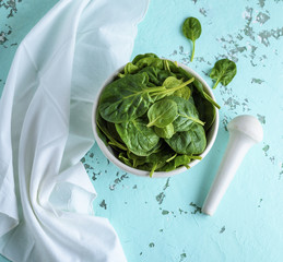 raw green spinach leaves in a white ceramic bowl