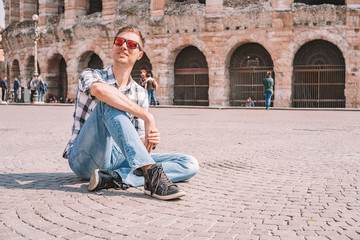 Verona, Italy. April 10, 2018. Young man exploring romantic Verona old town near the colosseum and city market.