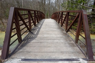 Red metal and wooden bridge on a nature trail.