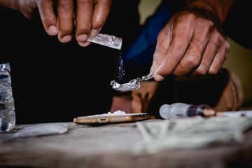 Closeup man using heroin. Narcotic overdose.man addict using cocaine drugs.Drug heroin addiction.Drug abuse concept,