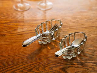 Silverware utensil holders with forks and spoons on wood table