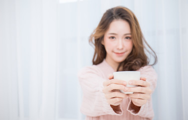 Young beautiful asian woman her hands holding a cup of coffee morning winter time in her white bedroom. Happy cheerful relaxing in cold winter concept banner