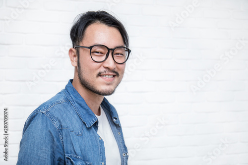 7c2b4074653 Attractive smile handsome positive asian nerd man. Close up portrait of  asian nerdy man wearing eye glasses over white background.