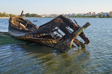 Old skeleton of a destroyed and burned boat on the bank of the Seixal Bay. Lisbon. Portugal