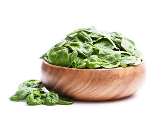 Spinach  leafs in wooden bowl isolated on white background