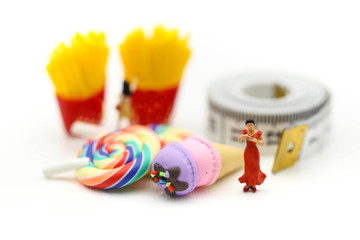 Miniature people : beautiful woman sitting on tape Measure with junkfood ,Healthcare and diet concept.