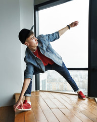 Teenager guy in denim jacket and baseball cap, jeans and sneakers dancing at window of dance studio. Hip-hop movement. Dynamics of modern dance