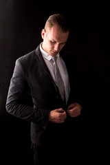 Handsome Businessman with black suit isolated on black background