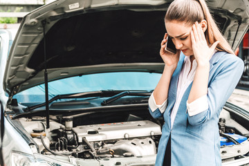 Woman calling for assistance with broken down car engine on street