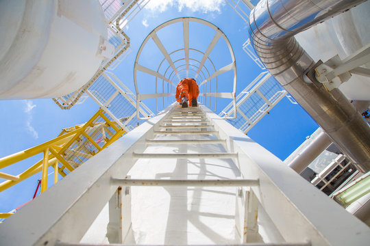 Process engineer climb up to the top of gas dehydration vessel to inspect and check abnormal condition of process and pipeline system in the oil and gas central processing platform.