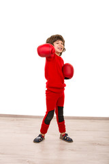 Cheerful boy showing fist in boxing gloves