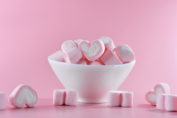Sweet marshmallows in the shape of heart in the ceramic cup with pink pastel background. Concept about love and relationship. Romantic Style, Creative for colorful greeting card.