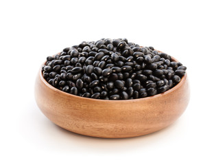 Raw  black beans in wooden bowl isolated on white