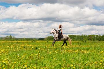 Foto op Aluminium Paardrijden Woman riding on grey horse in the field