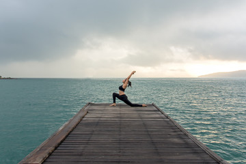 Healthy woman lifestyle balanced yoga practicing meditate and energy on the bridge in morning the seashore. Healthy Concept.