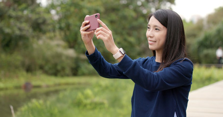 Woman taking photo with cellphone at outdoor
