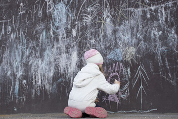 little girl on her knees painting on a large wall with chalk