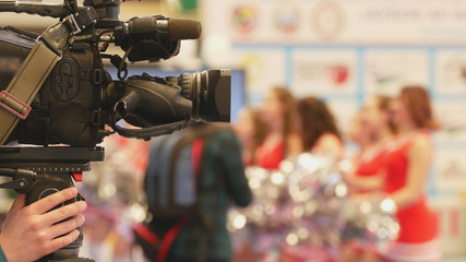 Camera in front of girls cheerleaders at the karate championship