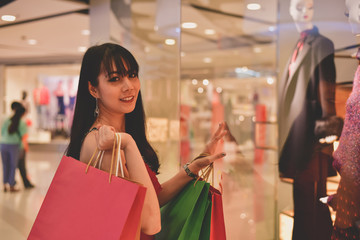 Shopping Concept. Asian girls are shopping in the mall. Beautiful women are happy to shop in the mall. Beautiful girl walking in the mall.